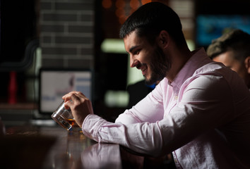Side view - young positive male hipster with bristles smiling and drinking whiskey during celebration of event