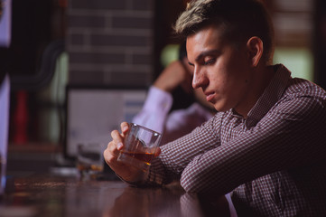 Side view - sad young hipster man looking at glass of whiskey and thinking about something sitting at the bar