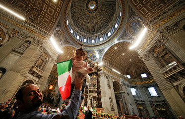 A migrant holds his child waving an Italian flag as Pope Francis leads a special mass to mark International Migrants Day in Saint Peter's Basilica at the Vatican