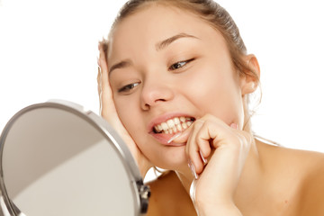 young girl looking her teeth in the mirror on white background