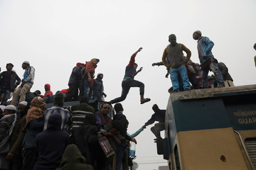 A commuter jumps between train compartments as they gather to attend Akheri Munajat, the final supplication during Biswa Ijtema in Tongi, on the outskirts of Dhaka