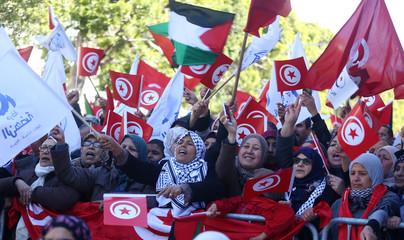 People wave national flags during demonstrations on the seventh anniversary of the toppling of president Zine El-Abidine Ben Ali, in Tunis