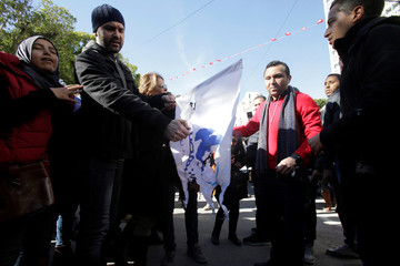 Protesters burn al Nahda party flag during demonstrations on the seventh anniversary of the toppling of president Zine El-Abidine Ben Ali, in Tunis