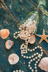 The pirate's treasure - white pearls and shells on blue wooden background, vintage fashion concept