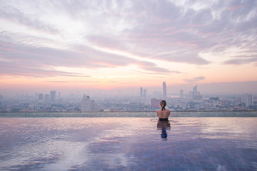 Young lady watching the sunrise at the infinity pool with city view. Thailand, Bangkok.