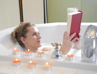 Frau liest Buch in Badewanne