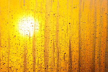The bright sun through the glass window. Sunrise in yellow red tawny tints. The drops of water on the glass surface. Ideal background for the illustrations and collages.