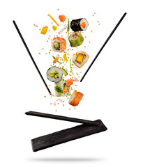 Flying pieces of sushi with wooden chopsticks and stone plate, isolated on white background.