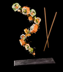 Flying pieces of sushi with wooden chopsticks and stone plate, isolated on black background.