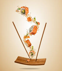 Flying pieces of salmon sushi with wooden chopsticks, separated on beige background