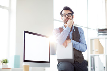 Handsome businessman with document looking at camera with computer monitor behind