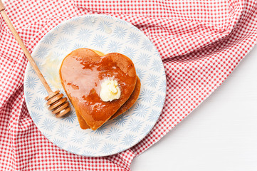 heart shaped pancakes on a light background. the concept of a festive breakfast for Valentine's Day or a pleasant surprise for a loved one