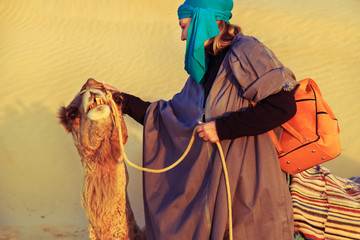 Woman with a camel in the Sahara desert.