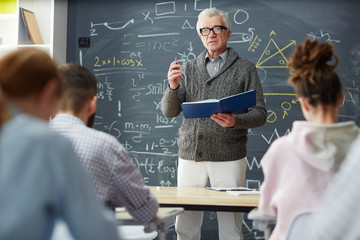 Mature teacher with open manual book explaining his students algebraic formulae