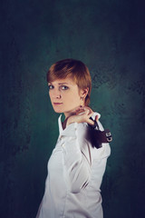 Woman with short hair holding a gun in her hand.
