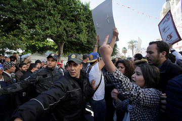 Policemen and people react during demonstrations on the seventh anniversary of the toppling of president Zine El-Abidine Ben Ali, in Tunis