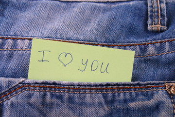 Paper note with the inscription I love you, with love peeps out of the pocket of jeans trousers. The concept of the day of lovers. St. Valentine's Day.