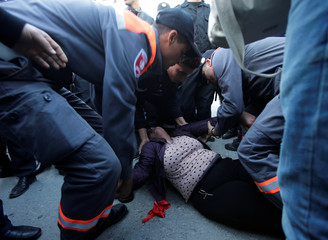 A woman faints during demonstrations on the seventh anniversary of the toppling of president Zine El-Abidine Ben Ali, in Tunis