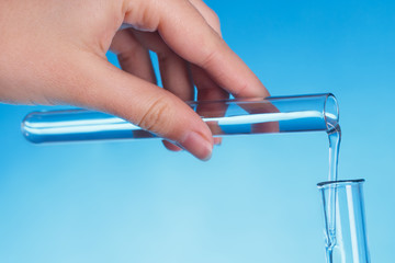 Scientist`s hand holds laboratory glass test tube with pure liquid, pours into other, makes experiment in research lab, blue background. Chemical solution in flask or glassware. Research concept