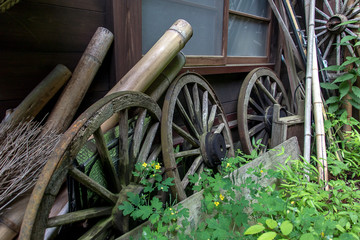 The old wheels lean in one line about a wooden house in the village