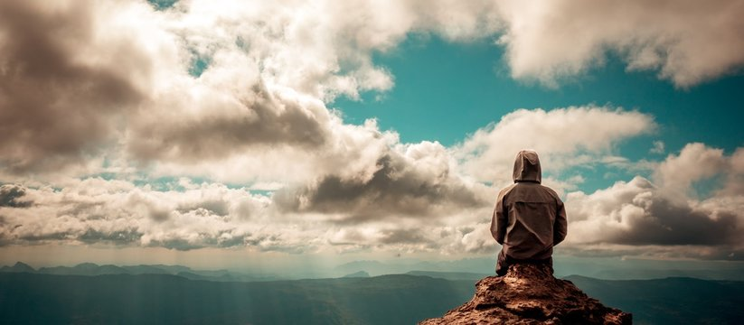 Lonely man sitting on top of mountain cloudy sky