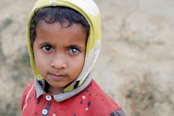 A Rohingya refugee child poses for a picture at Palong Khali camp, near Cox's Bazar