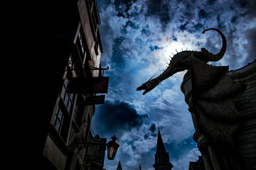 big fantasy dragon looming over houses in ancient magic town in obscure dim night