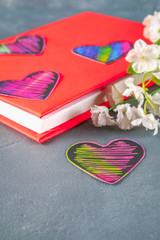 Black and pink hearts on a book in a red cover and flowers on a gray concrete background. The concept of Valentine's Day. A symbol of love.