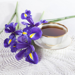 Violet Irises xiphium (Bulbous iris, sibirica) with cup of tea on white background with space for text. Top view, flat . Holiday greeting card for Valentine's Day, Woman's Day, Mother's Day, Easter!
