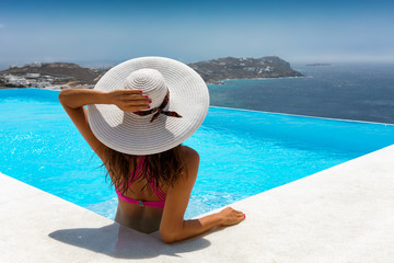 Elegante frau im Bikini und mit weißem Hut genießt ihren Urlaub in einem luxus Pool mit Aussicht