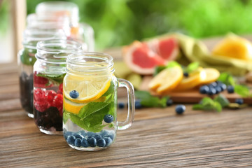 Mason jars of infused water with fruits and berries on wooden table