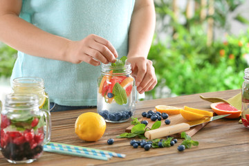 Woman preparing infused water with fruits and berries in mason jar