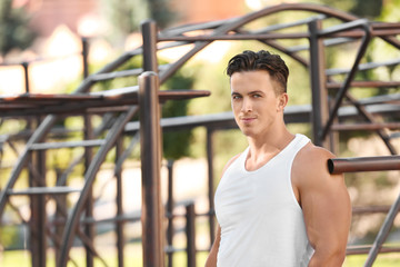 Handsome young man near pull-up bar outdoors
