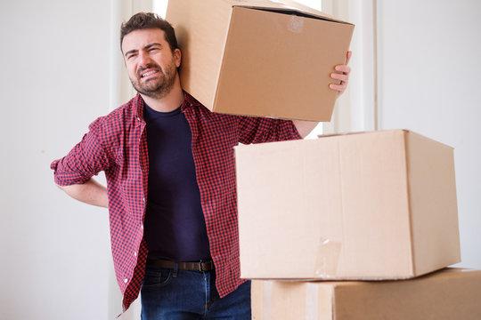 Man feeling back ache cramp moving heavy boxes