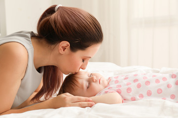 Young mother kissing her sleeping baby at home