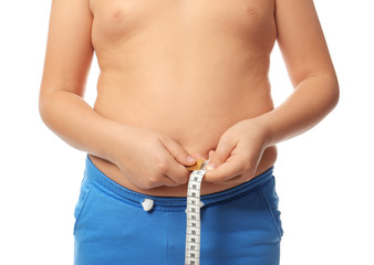 Overweight boy measuring his waist on white background, closeup