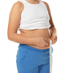 Overweight boy measuring his waist on white background