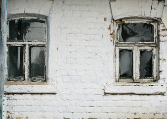 brick wall old rural house with two small old rickety Windows