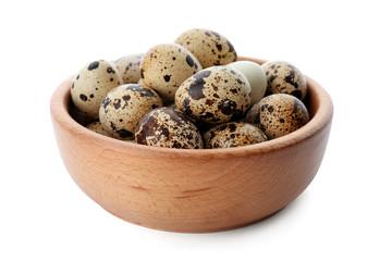 Quail eggs in bowl on white background