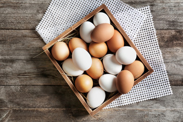 Chicken eggs in box on wooden table