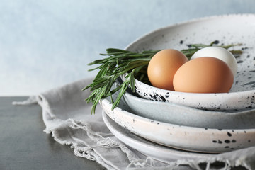 Plates with chicken eggs on table