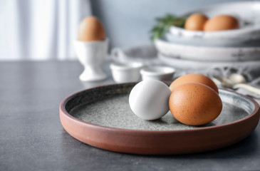 Plate with chicken eggs on table