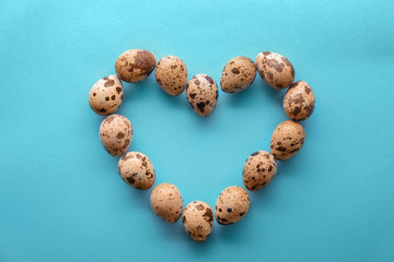 Heart made of quail eggs on color background