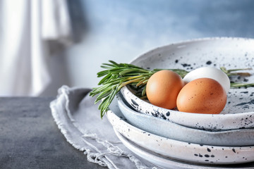 Plates with chicken eggs and rosemary on table