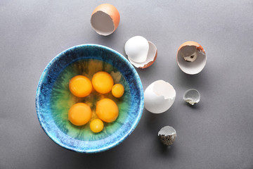 Bowl with raw chicken and quail eggs on table
