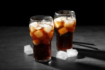 Cold cola in glasses on dark background