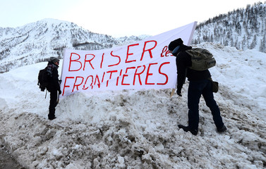 "Demonstrators hold a banner reading ""Destroy the borders"" as they march from Claviere in Italy to Montgenevre in France to ask for open borders for migrants"