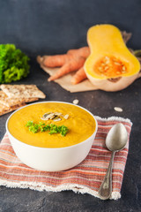 Bowl of Roasted pumpkin and carrot cream soup with parsley and pumpkin seeds on the dark stone served table with ingredients. Selective focus, Copy space.