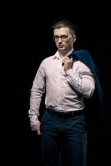 Confident elegant business man with glasses looking at camera over black studio background. on man s shoulder holds a jacket