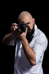 Photographer with camera. Male photographer with beard in a white shirt taking photon over black background